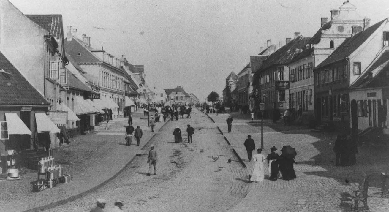 """Ahlgade, Holbæk ca.1910, set fra hjørnet af Lindevej imod vest. Bemærk renæssancegavlen, som stadig findes indemuret imellem Nordeas bygning og """"Klosterhus"""" på hjørnet af Nygade."""